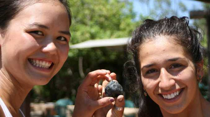 LUCKY FIND: Canadian backpackers Jenny and Fianata check out the extraordinary sapphire found in the Central Highlands Gemfields last week.