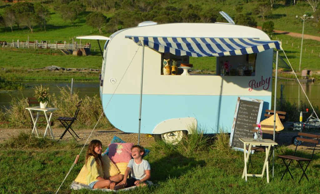 VINTAGE COFFEE: Sophia Willson and Roman Willson enjoy a laugh together as they relax in front of their mum's (Rachael Willson) new business Ruby Caravan. (Inset) Owner Rachael Willson busy making coffee.