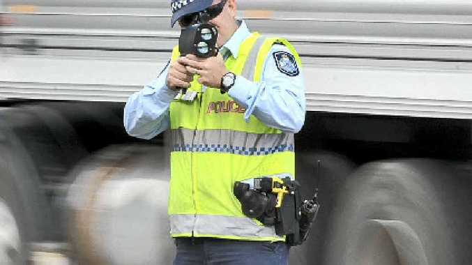 ON TARGET: A police officer uses a radar to catch motorists