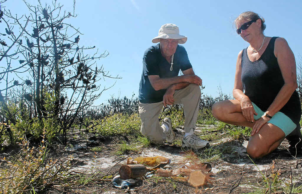 RUBBISH REVEALED: Lennox Head Landcarers Malcolm Milner and Shaun Eastment inspect some of the rubbish revealed following the fires in the heathland north of the village in late December.