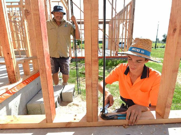 Relaxed Living Homes builder Craig Otto and apprentice Ben Thiele tighten off cyclone tie-down rods that keep the building attached to the slab; a requirement for building in a cyclone-prone area.