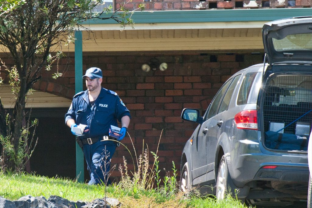 A policeman removes evidence after a search of a Mastrocolas Rd residence on Thursday afternoon.