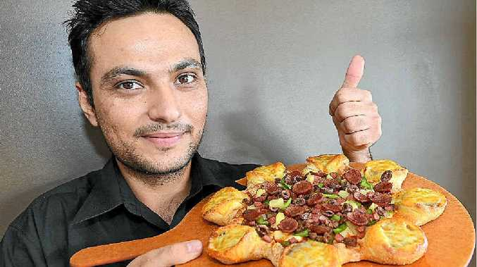 DIVIDING OPINION: Pizza Hut store manager Sonu Hayer with the new cheeseburger pizza.