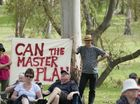 Kylie Goldthorpe and Mark Sutherland hold a protest sign at a community meeting in Garnet Lehmann Park.