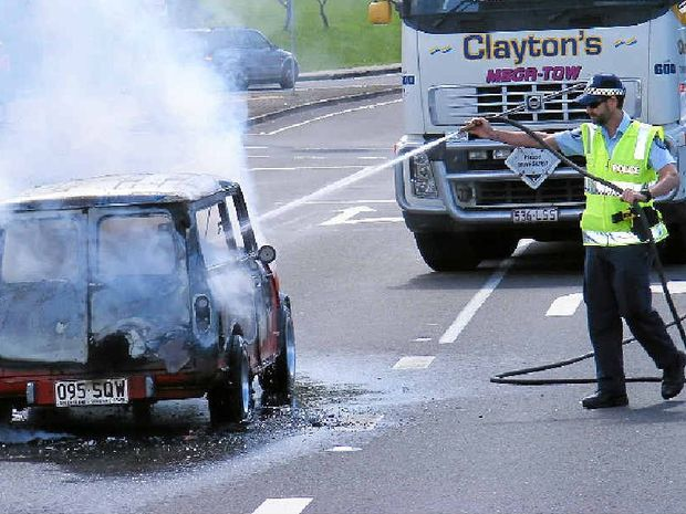 RESTORATION RUINED: A police officer helps hose a burning 1978 Leyland Mini station wagon. The rare car, which was being restored, caught fire on Buderim-Mooloolaba Rd last year.