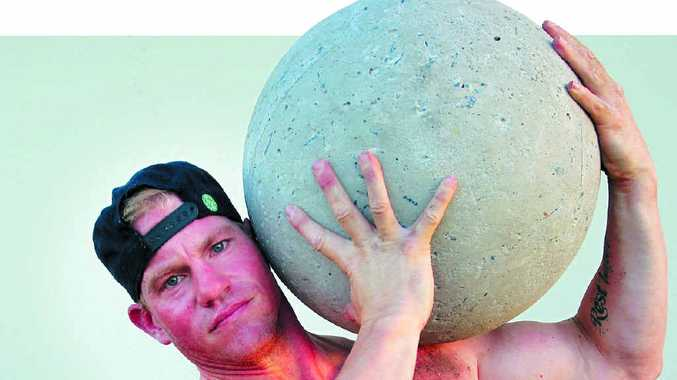 ATLAS: Caloundra's Kurt Southam hoists a concrete ball as he prepares for the Fit Bloke Challenge in Sydney in April.