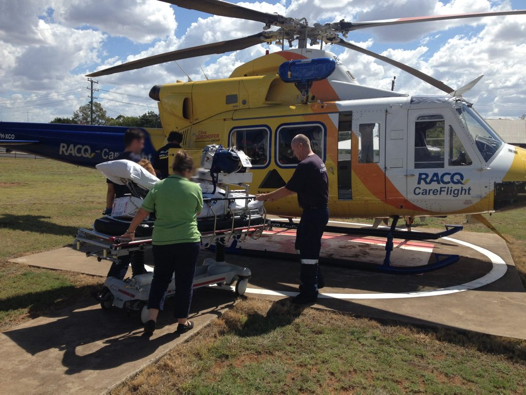 Careflight crew members load the boy into the helicopter.