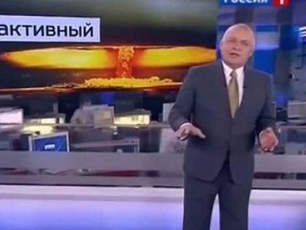 Dmitry Kiselyov speaks in front of an image depicting nuclear extermination.