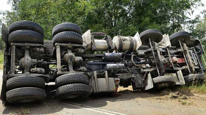 GOING NOWHERE: A waste-carrying truck that overturned on Swanbank Rd, Swanbank, yesterday and lost its load.