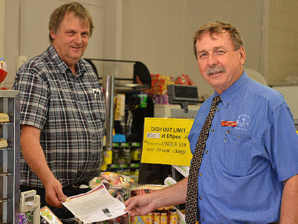 Tim Long from Long's Crescent Road One Stop Shop with Gympie High principal Murray Wegner and one of the leave passes students will have to present to prove they are not wagging school.