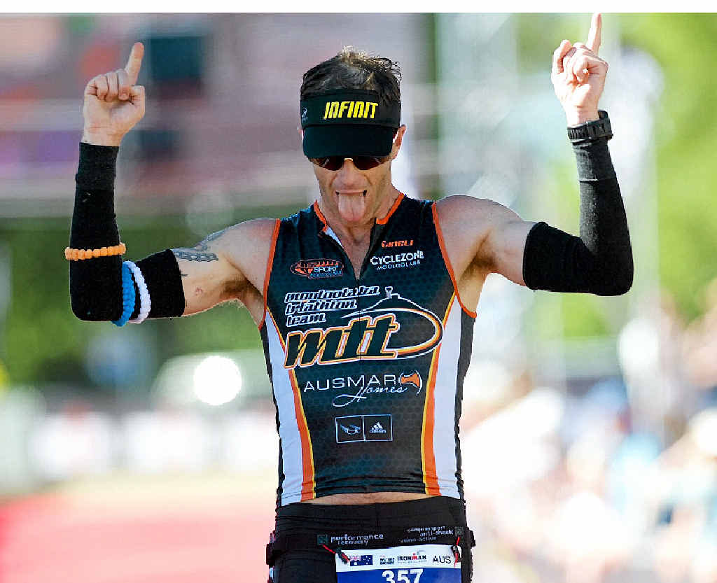 CELEBRATION TIME: Scott Farrell crosses the line at Ironman New Zealand.