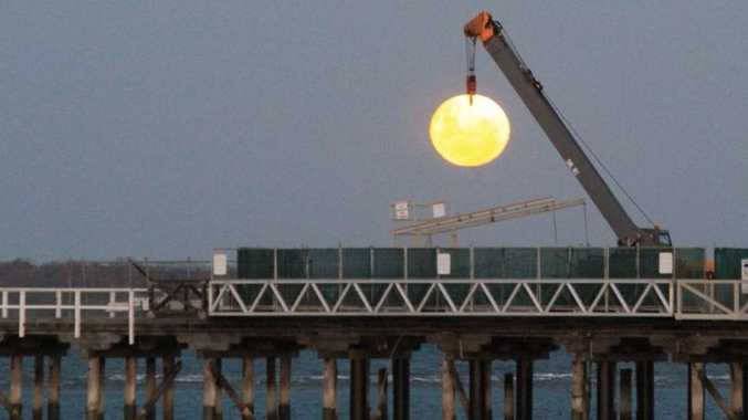 Erica Neate was in the right place with her camera to witness the crane refurbishing the Urangan Pier seemingly pluck the moon from the sea.