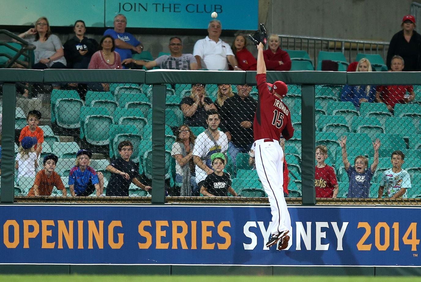 The Arizona Diamondbacks' Mark Trumbo jumps in an attempt to catch a home run ball from Team Australia's Australia's Tim Kennelly during their exhibition baseball game at the Sydney Cricket ground