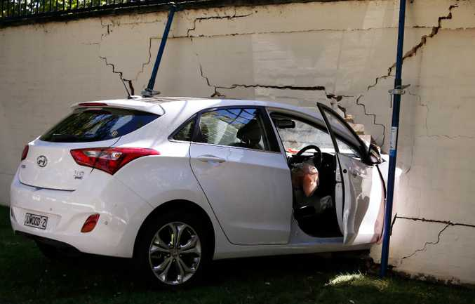 A car is seen crashed on a wall of