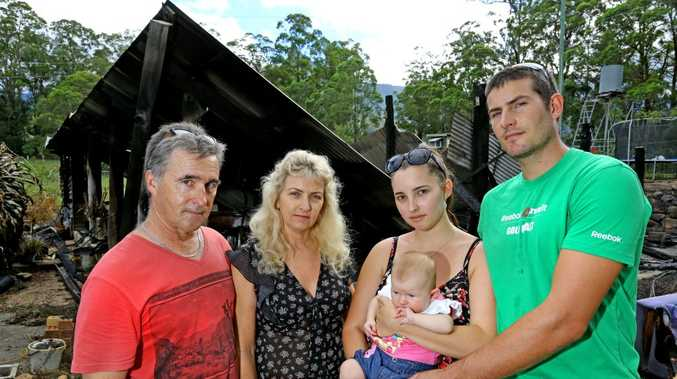 Terry, Jenelle and Arenea Norris with her boyfriend Crusoe Bower and daughter Lyla at what remains of their burnt down house at Pumpenbil.