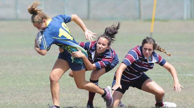 Fraser Coast Invitational Rugby 7's Tournament - Kelly O'Reilly from Xavier gets tackled by Lily Olujic from FCAC in the open girls contest.