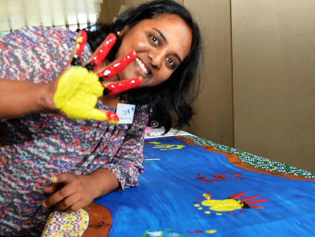 Mackay GP Manjula Denkanikota puts her handprint on a canvas to show support.