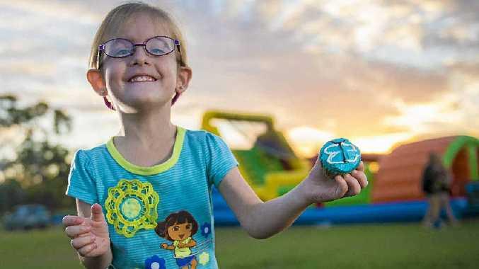 Lillian Evans, 3, enjoys a blue cupcake during a Go Blue Autism Queensland fundraiser in Blain Park, Gladstone.