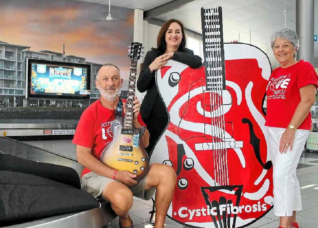 MUSICAL RAFFLE: Alan and Jenny Tunks, of Ballina, with Ramada Hotel and Suites general manager Karen Whiteford (centre) and the Gibson guitars being raffled in support of cystic fibrosis research.