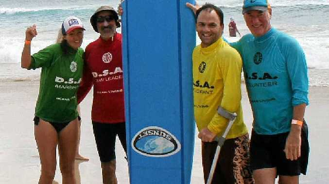 Organiser Margreet Wiegers, volunteer Ian Cohan, participant Tim Winton-Brown and volunteer Paul McNeil soak up the fun at the Disabled Surfing Association surf day at Clarkes Beach Byron Bay on Saturday.