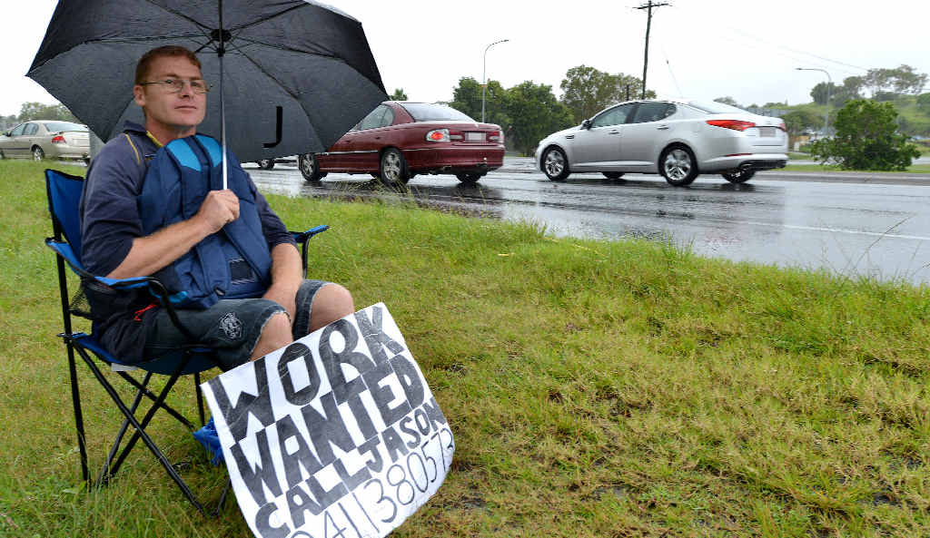 Jason Wheatley didn't let heavy rain stop him as he sat on Mackay Bucasia Road at Mount Pleasant looking for work.