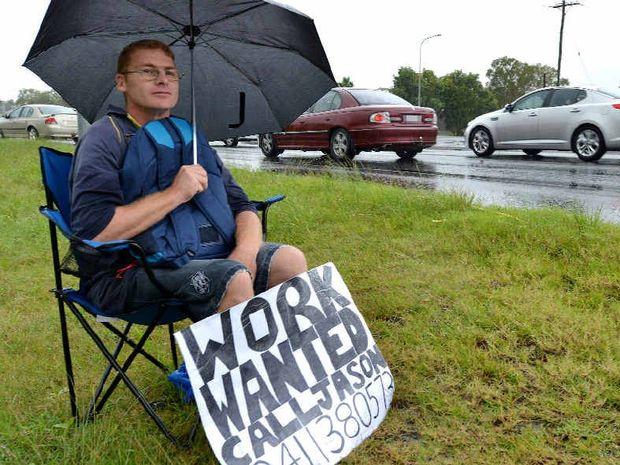 Jason Wheatley didn't let heavy rain stop him as he sat on Mackay Bucasia Road at Mount Pleasant looking for work.