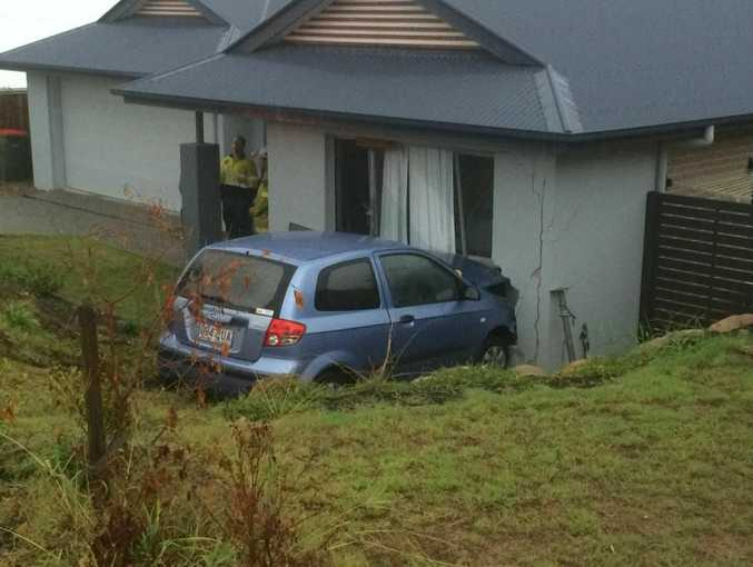 A car slid down an embankment in wet weather, damaging a house in Riverstone Rise.