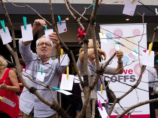 Phil Greed from North Coast TAFE pins a love note to the Story Tree.