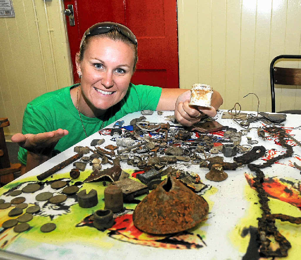 TREASURE TROVE: Tammy Bichel shows off some of the items found by metal detectors searching for the lost time capsules at Tallegalla State School.