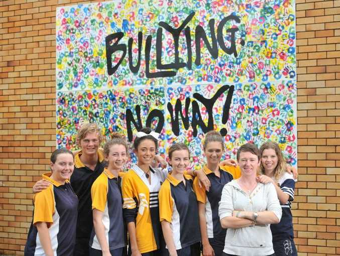 Gladstone State High teacher Niamh O'Sullivan with students Maddy Cushway, 17, Michael Eiser, 17, Taylah Crosbie, 16, Bree Smith, 16, Jillian McKewen, 17, Anna Williams, 16, Billie Chapman, 16, at the anti-bullying mural erected on Friday, National Day of Action Against Bullying and Violence.