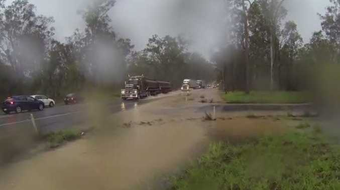 Some semitrailers and cars drove through the floodwaters on the Bruce Hwy near Tiaro on Sunday.