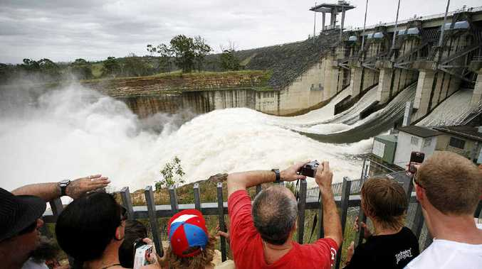 FLOODGATES OPEN: A picture from 2010 of all five spillway gates open at Wivenhoe Dam creating a boiling surge of racing water and a huge cloud of spray.