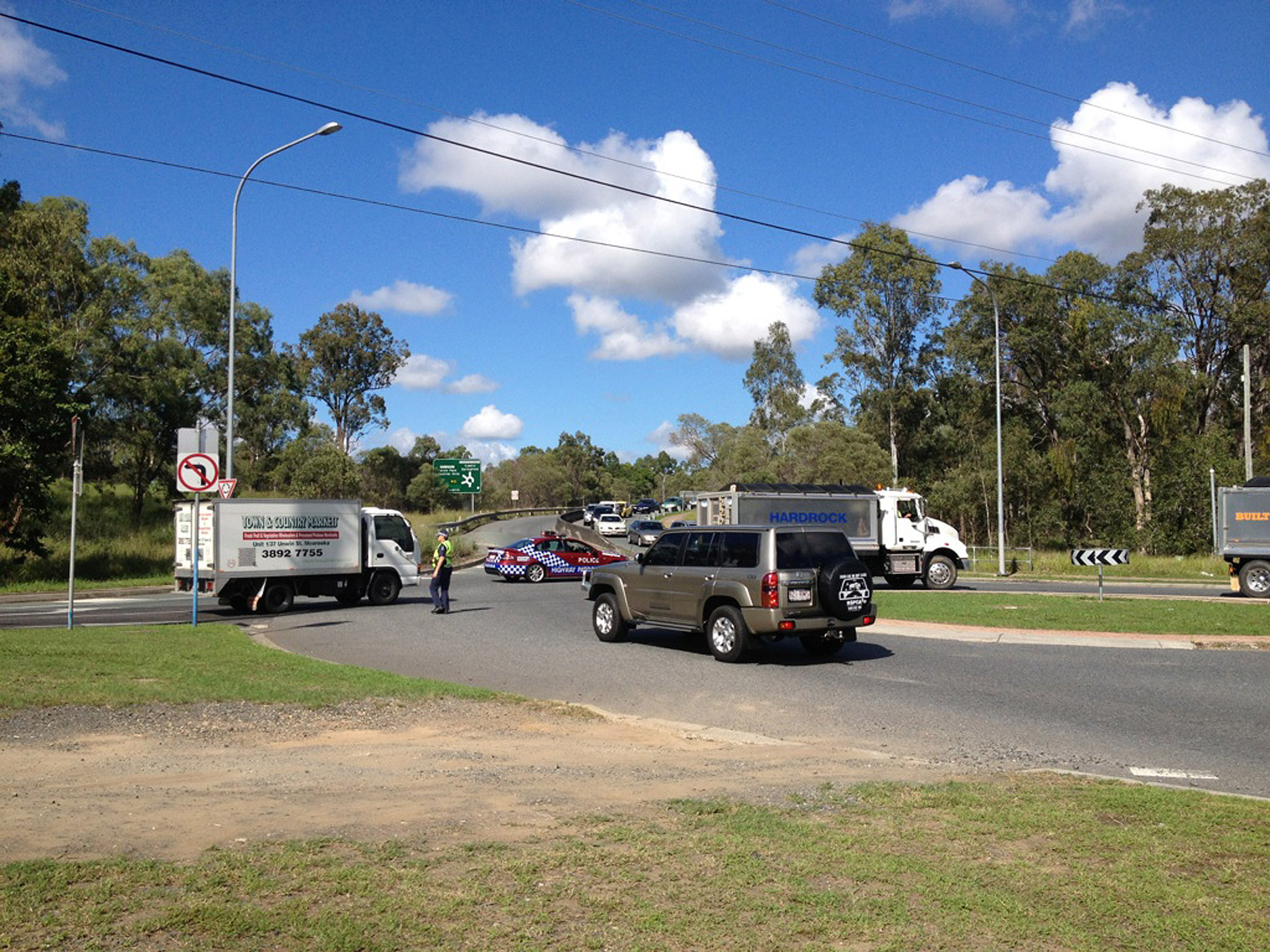 Police redirect traffic away from Mica Street (not visible) to the Formation Street roundabout at Carole Park.