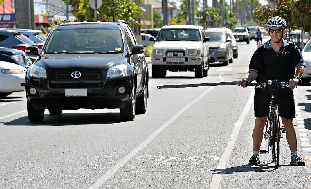 Rock N Road Cycles owner Ron Steel, a keen cyclist, demonstrates the one-metre rule from inside a cycling lane.