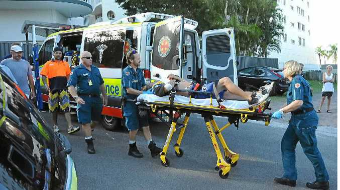 AMAZING ESCAPE: Paramedics stretcher the victim to a waiting ambulance.