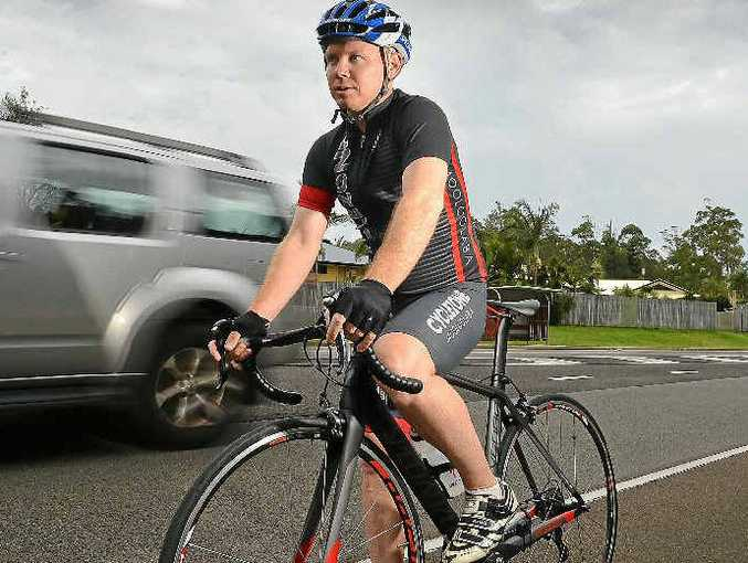 DANGER AHEAD: The new one-metre clearance law is tipped to cause fatalities. Cyclist Brett Reedman tackles a busy road.