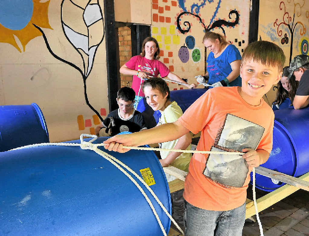 RAFT RIDE: Blake Denniss, 12, (front) at the helm of the raft being built for National Youth Week by (from left) Olivia Mison, 12, Matthew Gilliand, 14, Ebony Fallon, 15, Desirae Gilliand, 12, Jordan Gilliand, 13, and Flynn Geddes, 12.
