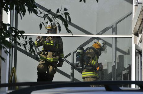 Firefighters return from the second level of the building. Photo Gen Kennedy / The Chronicle