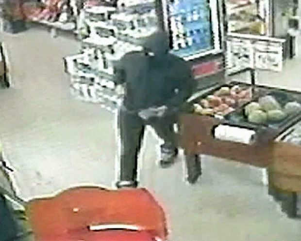 CCTV footage of an armed gunman police are seeking following a robbery at a Gladstone supermarket on Monday night.