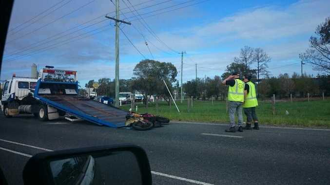 Tow truck operators load a motorbike onto the tray of their vehicle following a crash at St Helens.