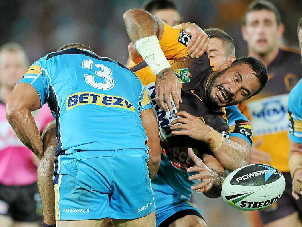 The Broncos' Justin Hodges knocks the ball on in a tackle against the Gold Coast Titans last night.