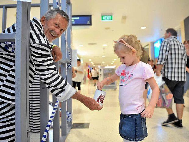 Imogen Stoneley, 4, helps community member Mac Hosking raise bail after he was locked in a mock jail.