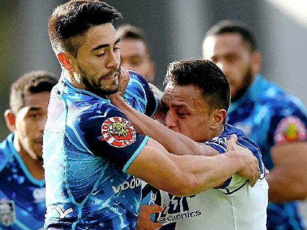 HELD UP: Sam Perrett (right) of the Bulldogs is tackled by Shaun Johnson of the Warriors in Auckland yesterday.
