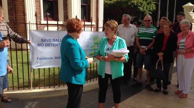 A petition against detention basins in Toowoomba's Ballin Dr and Garnet Lehmann parks is presented to Cr Sue Englart outside City Hall this morning.