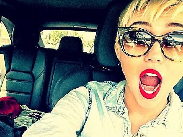 Singer Miley Cyrus takes a driving selfie.