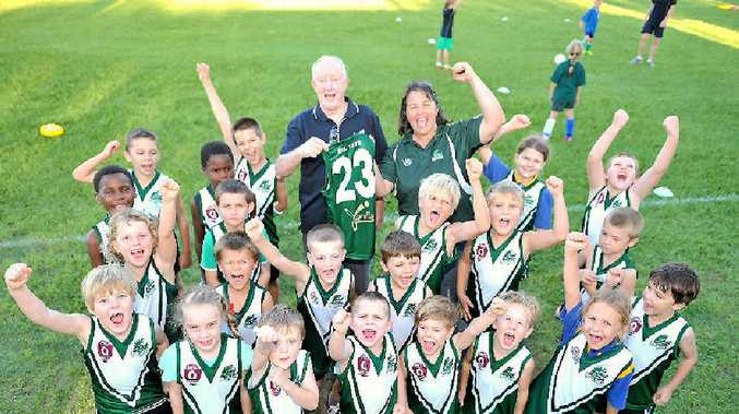 Yaralla president Col Collins and Gladstone Mudcrabs sub-junior co-ordinator Sheri Hope celebrate with juniors about receiving new guernseys for this season.