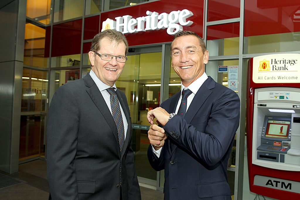 Queensland sporting legend Mat Rogers (right) models the M.J. Bale suit embedded with a contactless payment chip, along with Heritage Bank chief operating officer John Williams. Photo Contributed