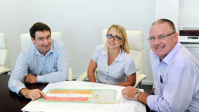 Win Constructions Queensland's Glen Winney and Rose McVeigh with Design Plus's Brett Turner look over plans for Christensen House.