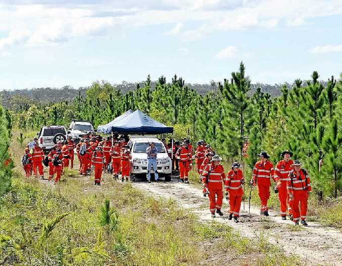 SKULL SEARCH TWO: Inspector Brett Long and SES volunteers sweep the Toolara State Forestry near Tin Can Bay yesterday.