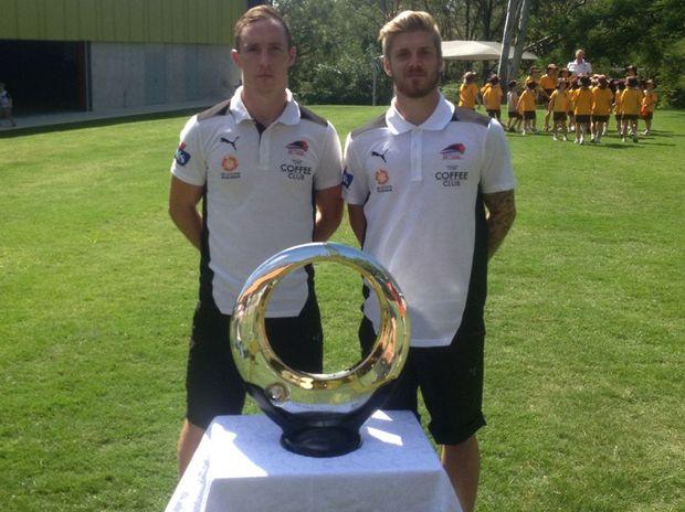 Roar stars Matt Smith and Luke Brattan were swamped by their young fans in Brisbane yesterday.